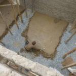 L'élaboration du sol des classes : le maçon lisse la couche de terre battue © Estelle Delahaye-Panchout