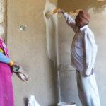 Après l'enduit à base de terre, application d'une couche de peinture. Cette peinture à base de yaourt permet de conserver les qualités respirantes du mur en terre (contrairement aux peintures acryliques) © Estelle Delahaye-Panchout