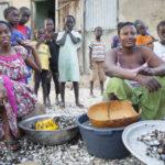 Femmes qui transforment les coquillages accompagnées de leurs enfants